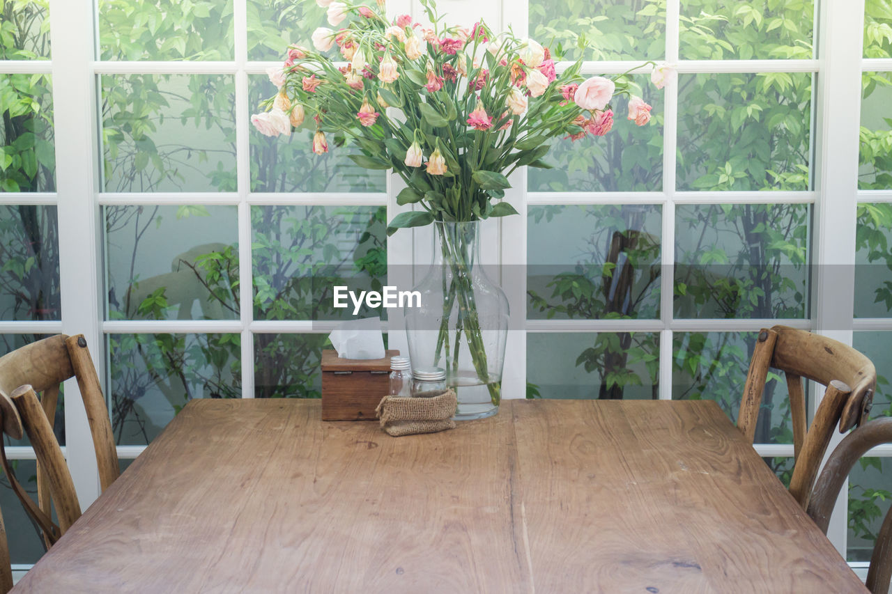 flower, plant, flowering plant, seat, chair, indoors, table, vase, home interior, no people, absence, window, furniture, nature, domestic room, glass - material, transparent, day, freshness, beauty in nature, flower head, flower arrangement, flower pot