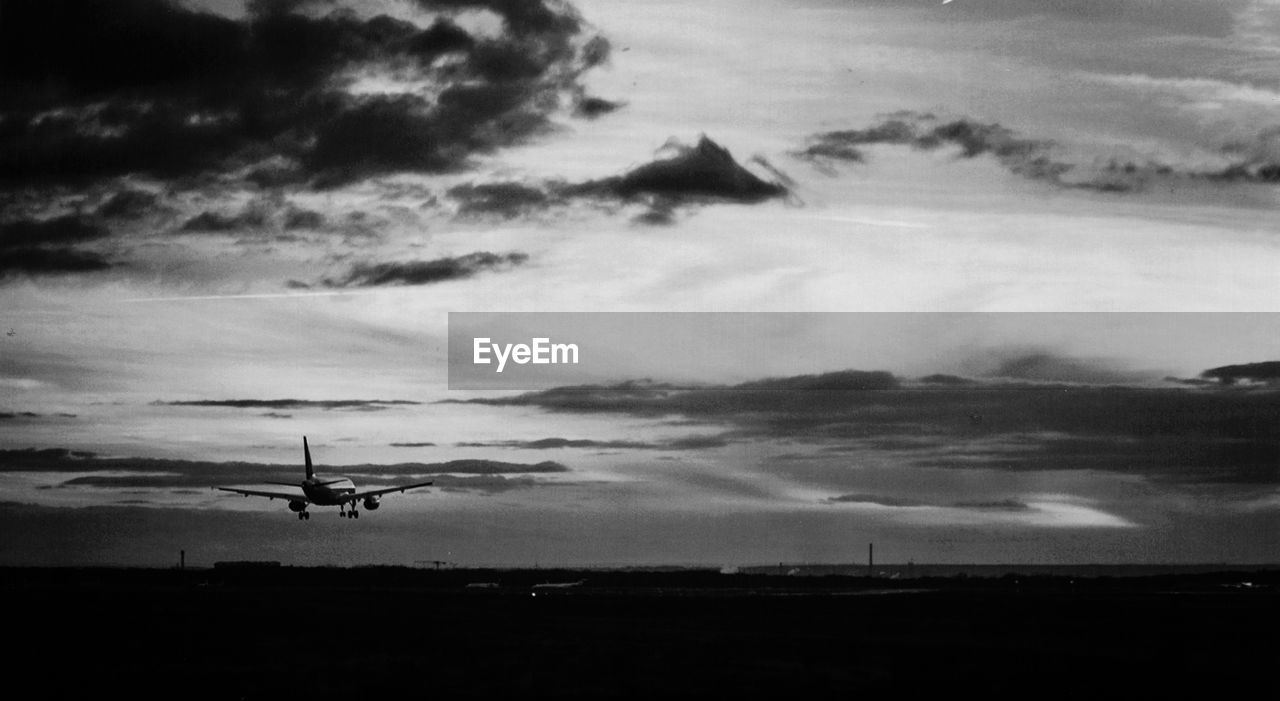 cloud - sky, sky, air vehicle, mode of transportation, airplane, flying, transportation, no people, nature, mid-air, environment, scenics - nature, silhouette, dusk, on the move, landscape, outdoors, beauty in nature, storm, plane