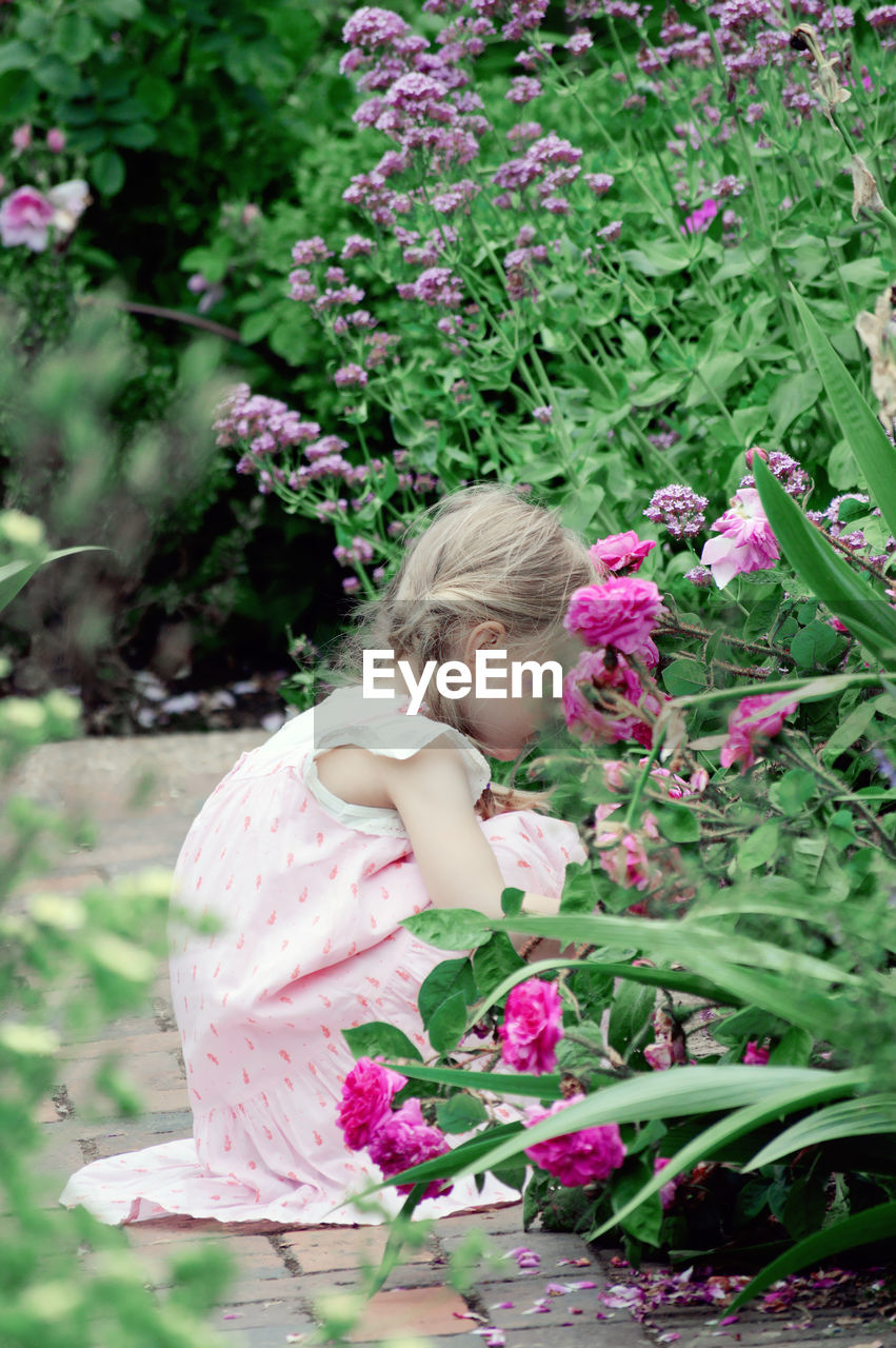 Girl crouching by flowering plant