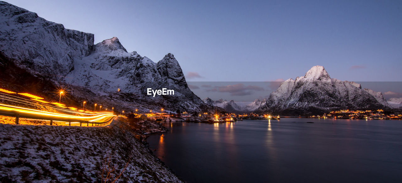 Light Trails Amidst Lake And Snow Covered Mountains Against Sky