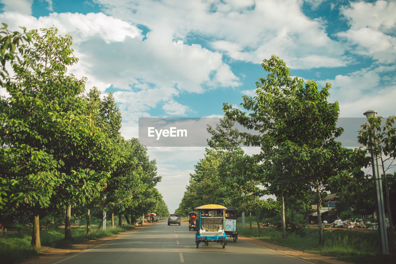 transportation, tree, plant, cloud - sky, mode of transportation, land vehicle, sky, road, nature, day, public transportation, city, street, green color, car, motor vehicle, travel, motion, outdoors, incidental people, treelined