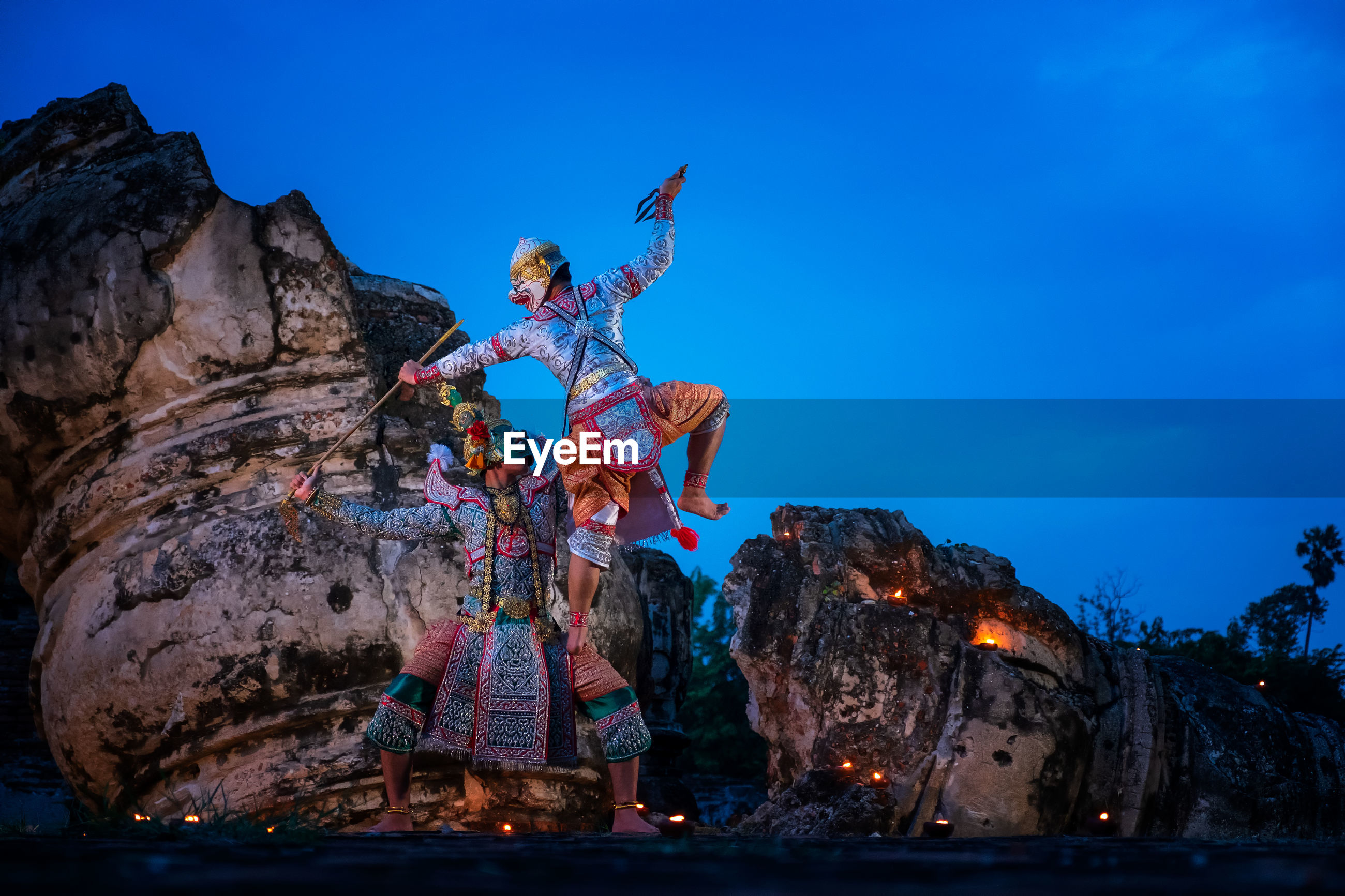 People in traditional clothing performing on rock formation against blue sky at dusk