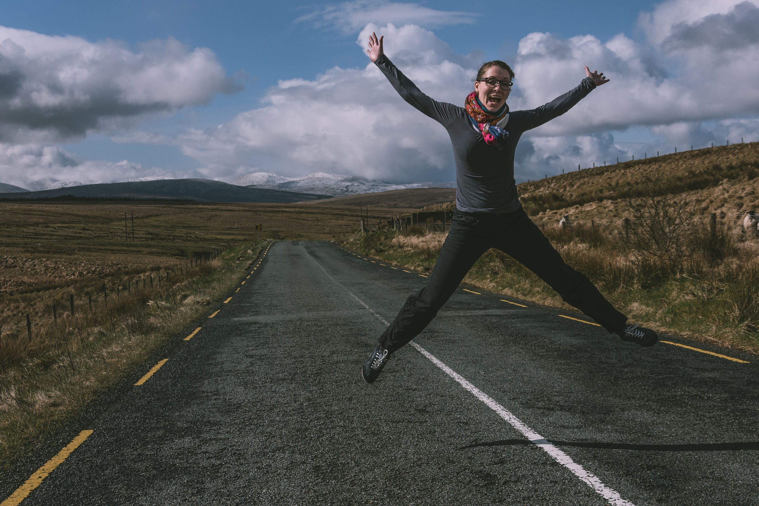 Playful woman jumping with arms outstretched on road against mountains