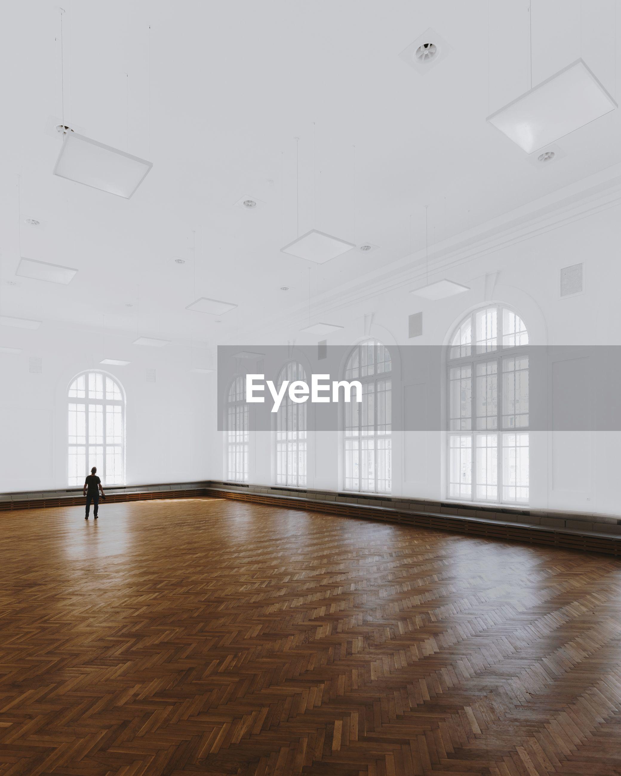 Rear view of man standing on hardwood floor