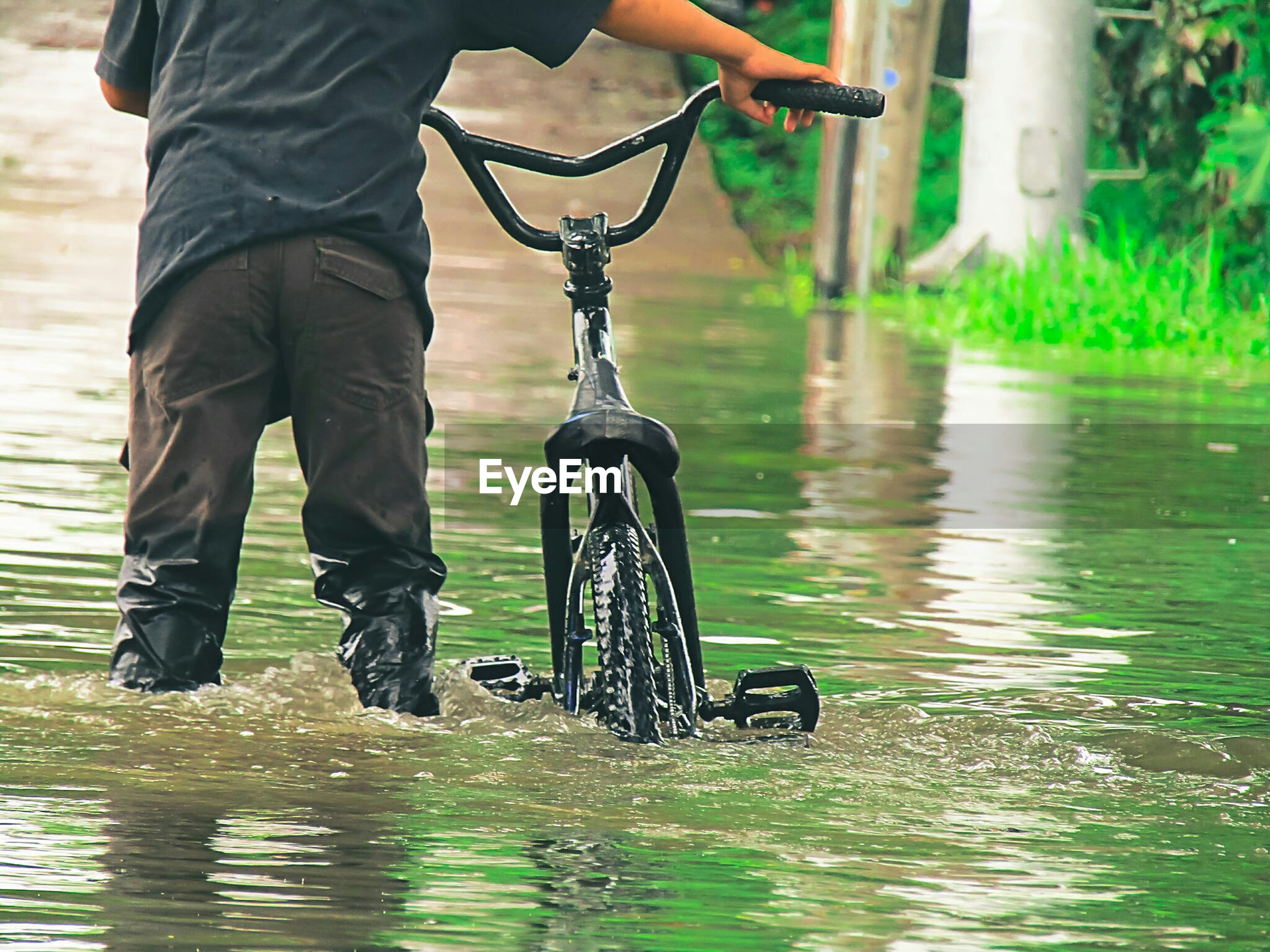 Midsection of man with bicycle standing in water