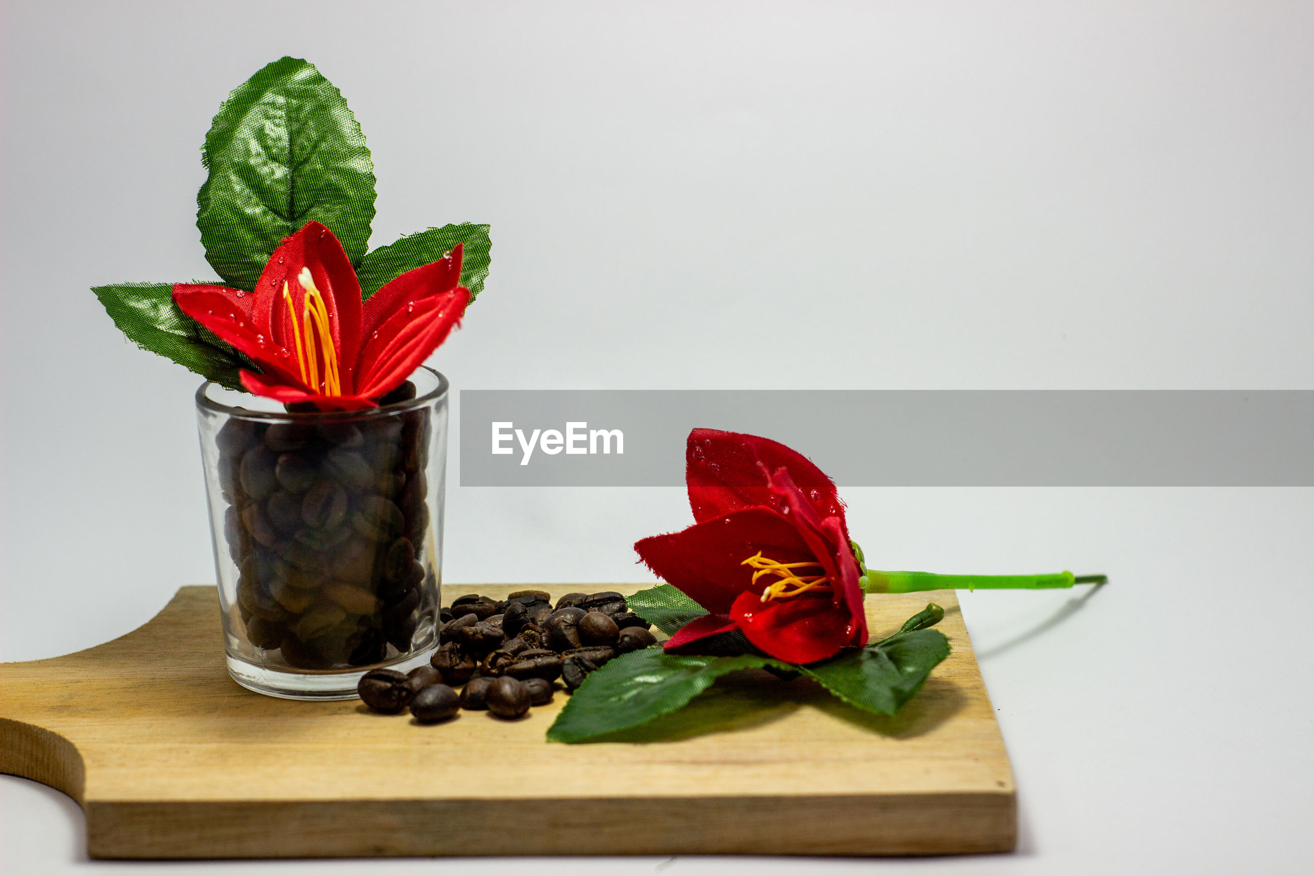 CLOSE-UP OF RED ROSE ON TABLE WITH LEAVES