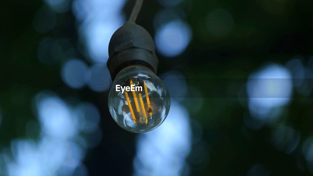 CLOSE-UP OF LIGHT BULB HANGING ON GLASS