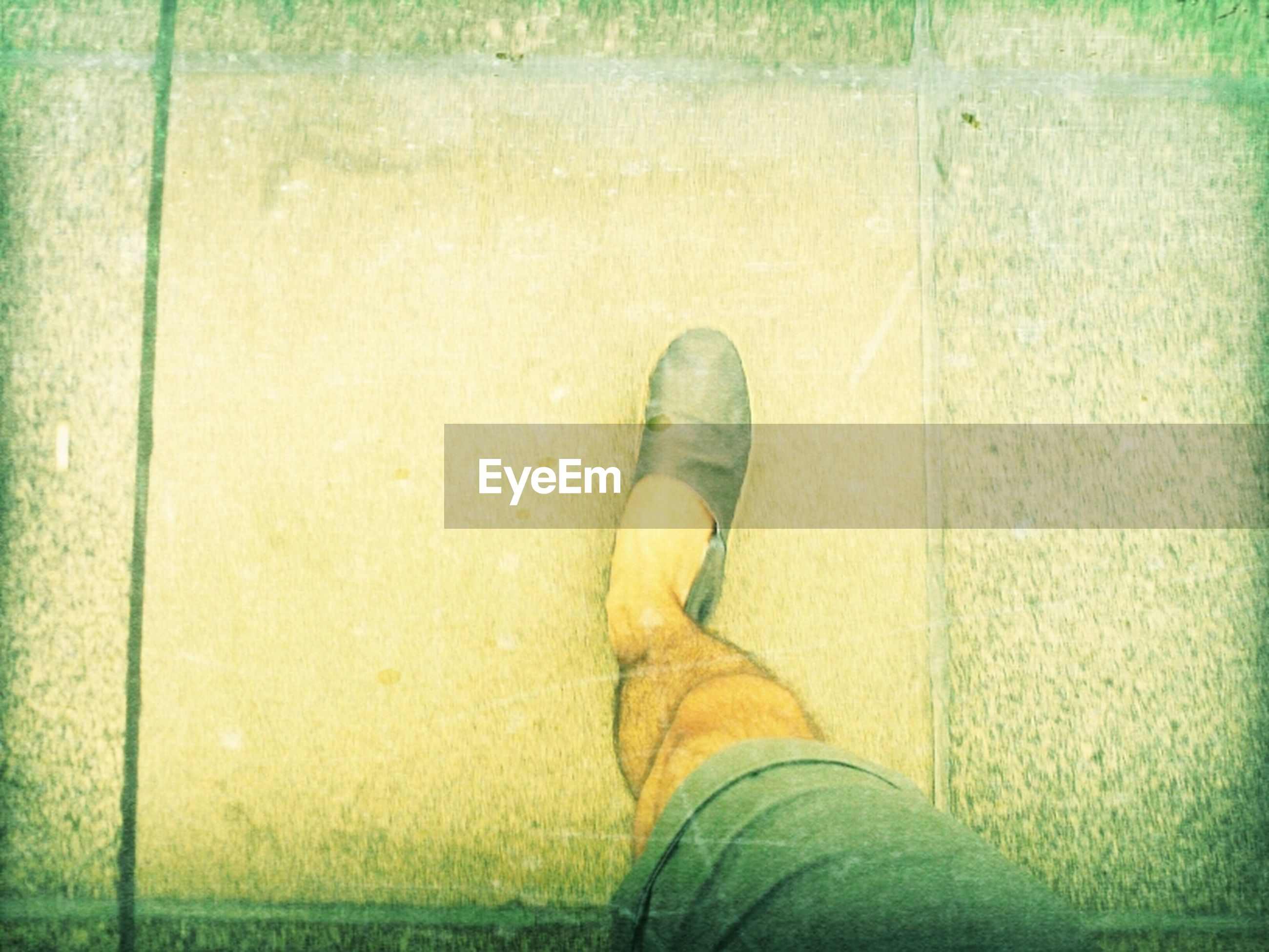 low section, person, shoe, personal perspective, lifestyles, human foot, footwear, standing, high angle view, jeans, relaxation, leisure activity, men, grass, legs crossed at ankle, casual clothing, day