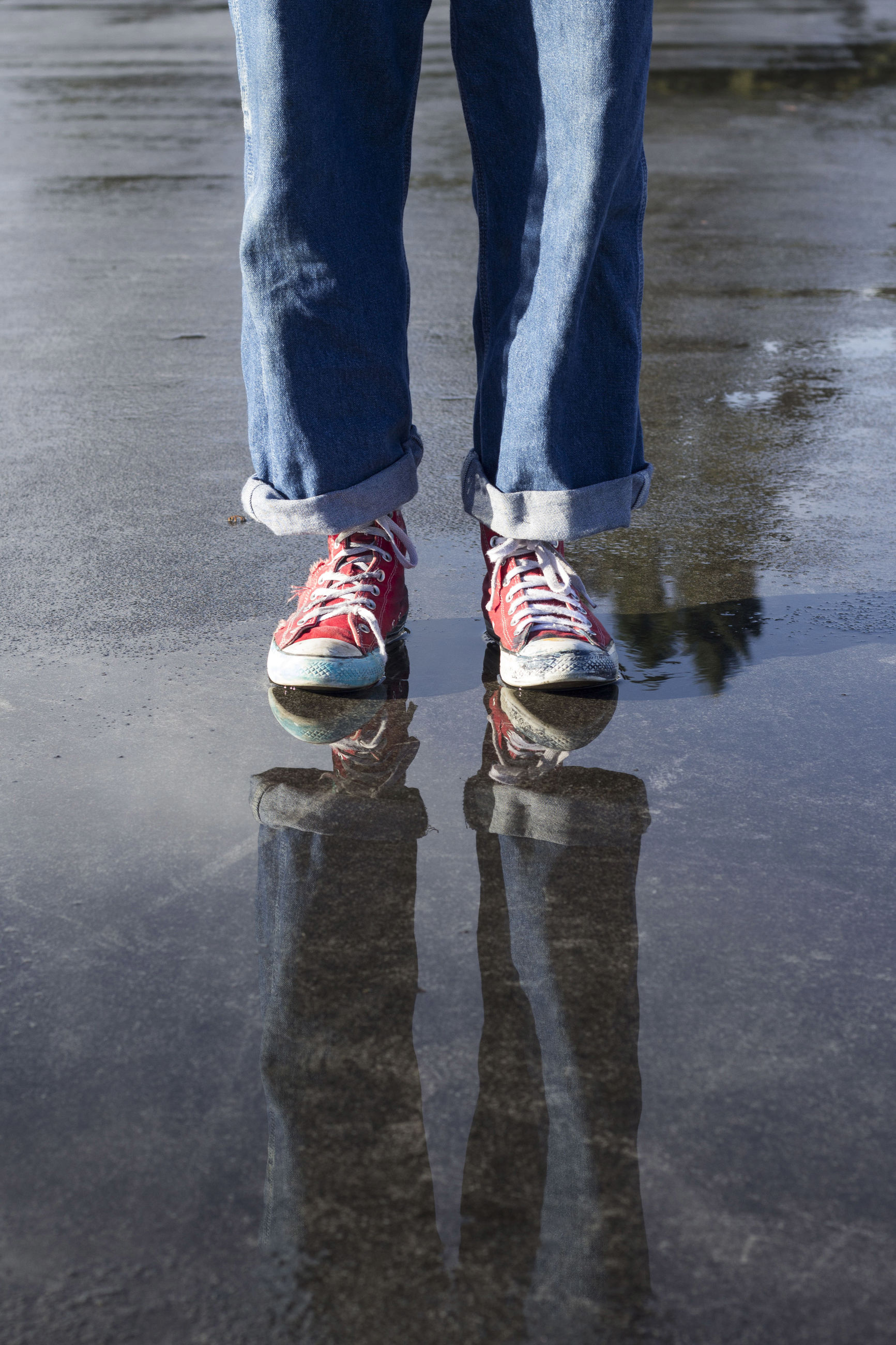 Low section of person standing by reflection on puddle