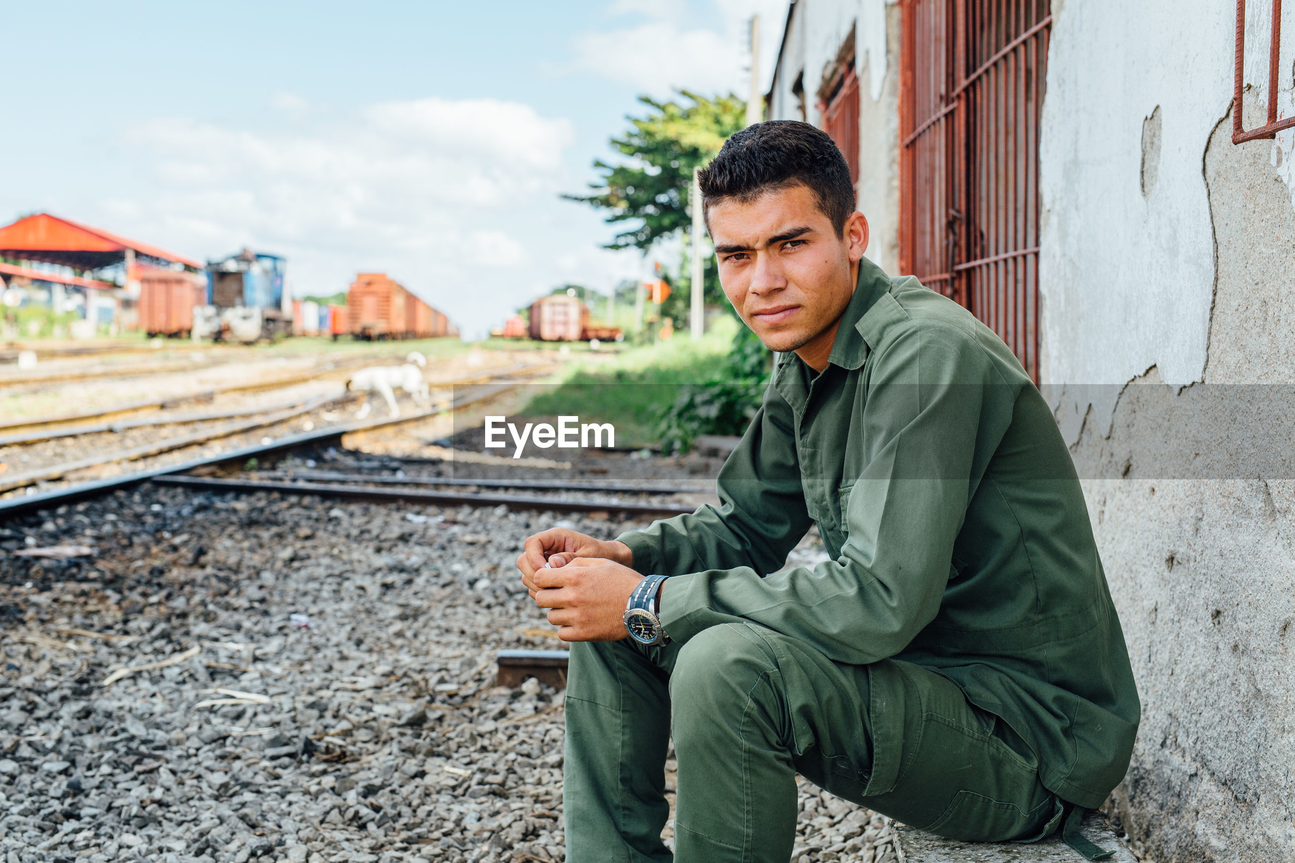 men, railroad track, only men, one man only, sitting, smart phone, one person, portable information device, business finance and industry, portrait, adult, human hand, outdoors, technology, human body part, people, day