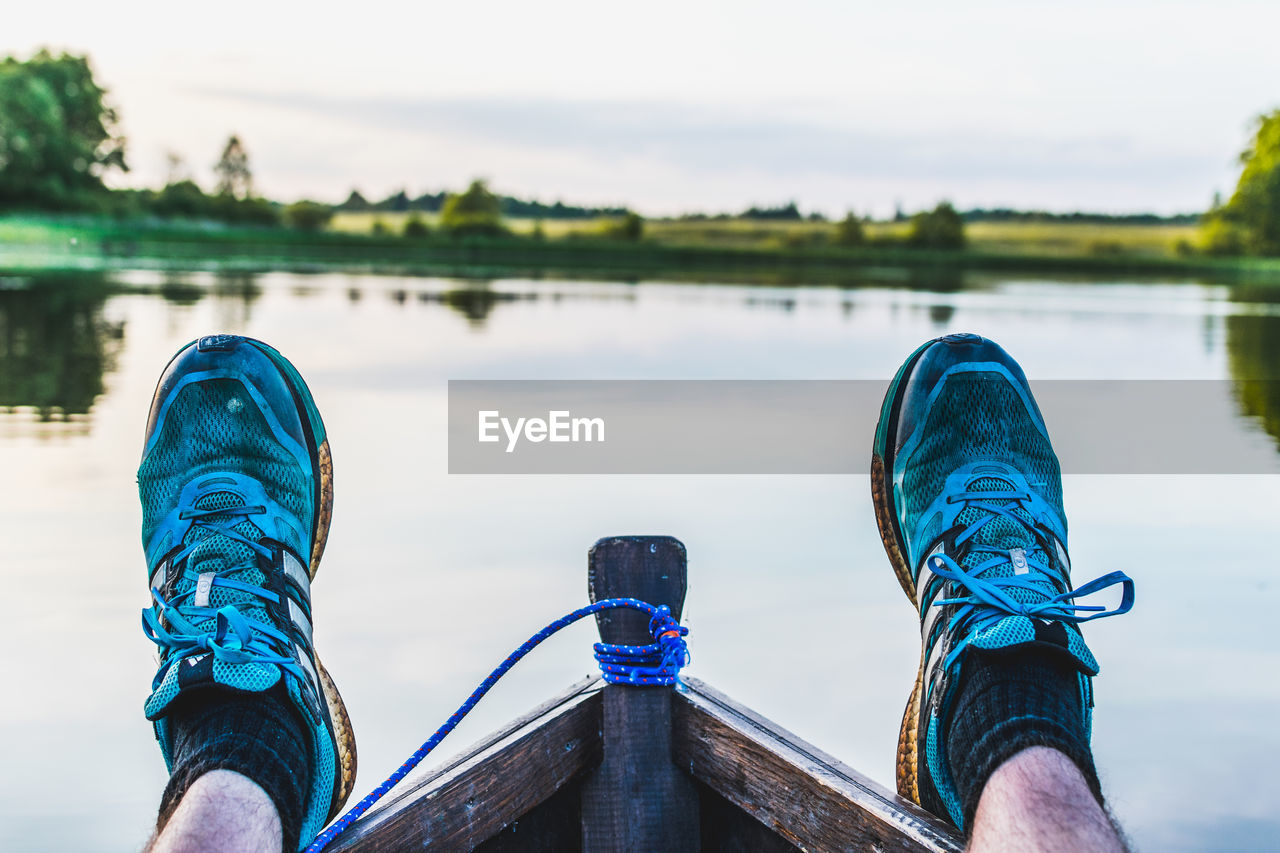 human leg, low section, shoe, balance, human body part, one person, blue, focus on foreground, day, water, outdoors, river, real people, leisure activity, nature, sky, adventure, men, beauty in nature, close-up, people