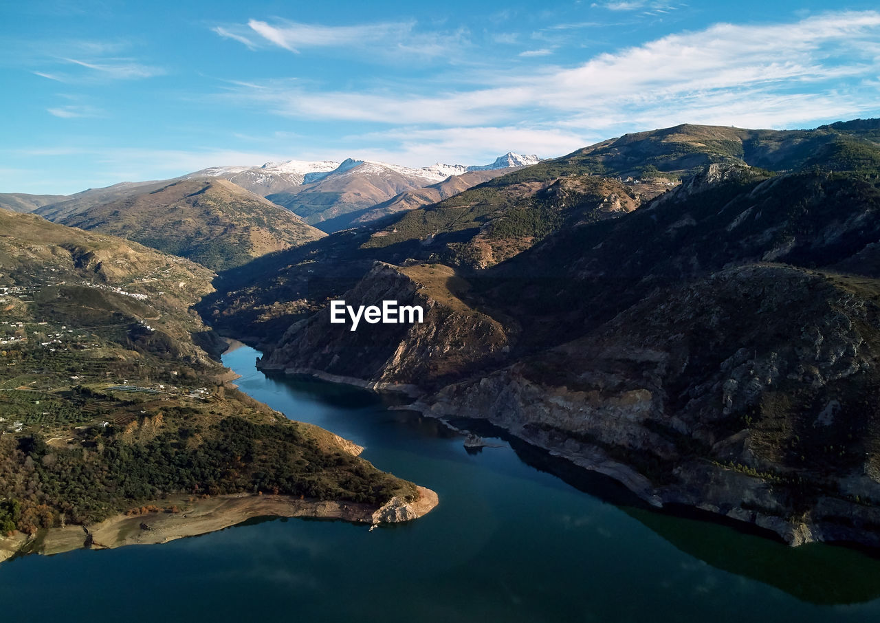 Aerial view of lake by mountains against sky