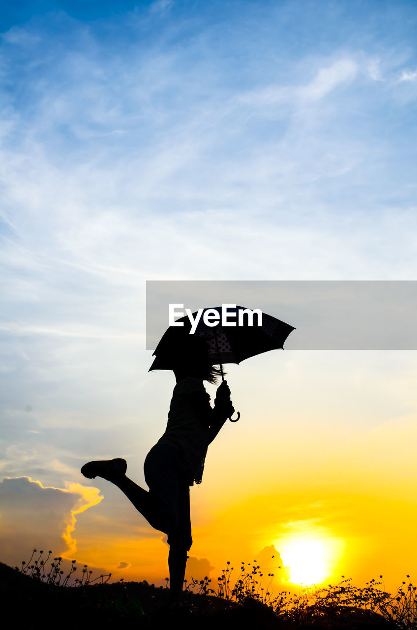 Silhouette Girl With Umbrella Standing Against Sky