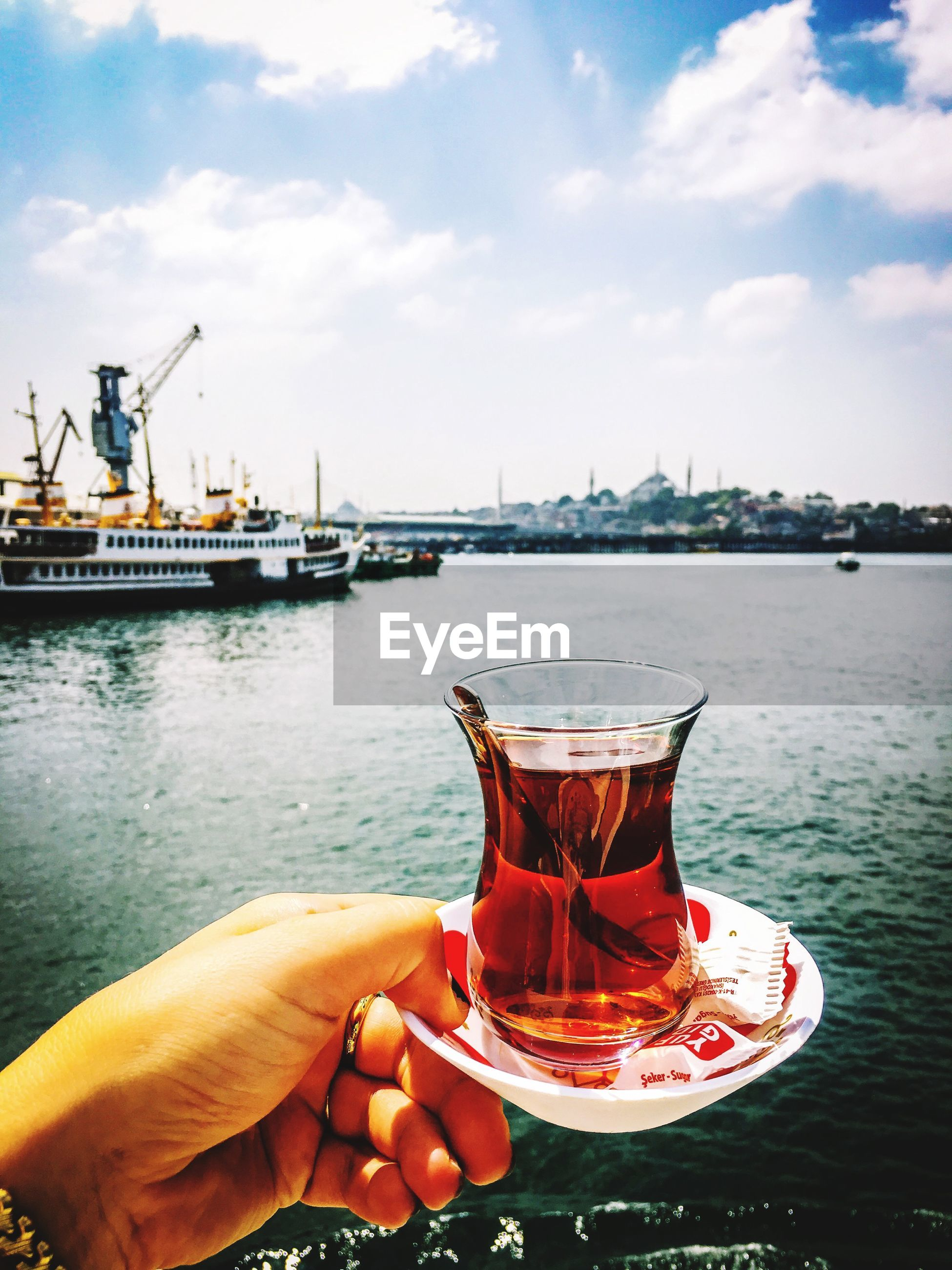 Person holding tea against sky