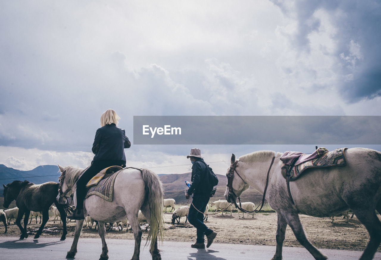 Rear woman riding horses by man on road against cloudy sky