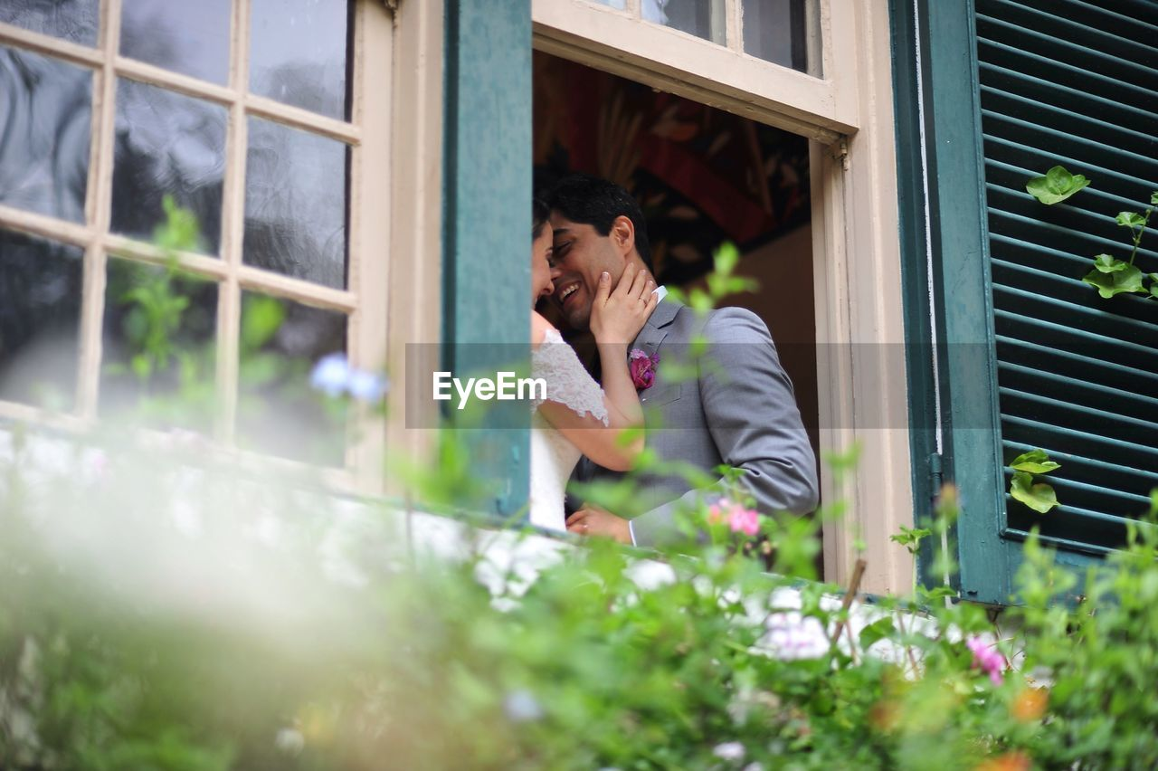 Low Angle View Of Bride And Groom Standing By Window