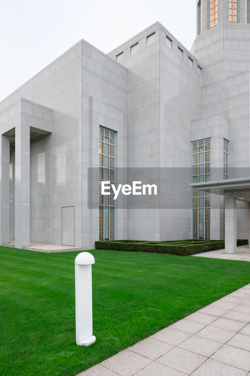 architecture, built structure, building exterior, grass, building, day, green color, modern, city, no people, plant, nature, outdoors, lawn, sky, office building exterior, glass - material, field, entrance, footpath