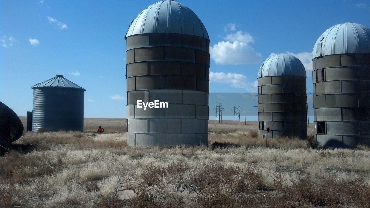Built Structures On Grassy Field Against Sky