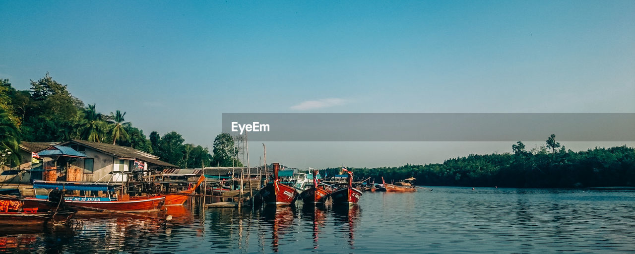 sky, water, nautical vessel, transportation, mode of transportation, waterfront, nature, tree, plant, group of people, day, real people, scenics - nature, beauty in nature, architecture, outdoors, built structure, travel, men
