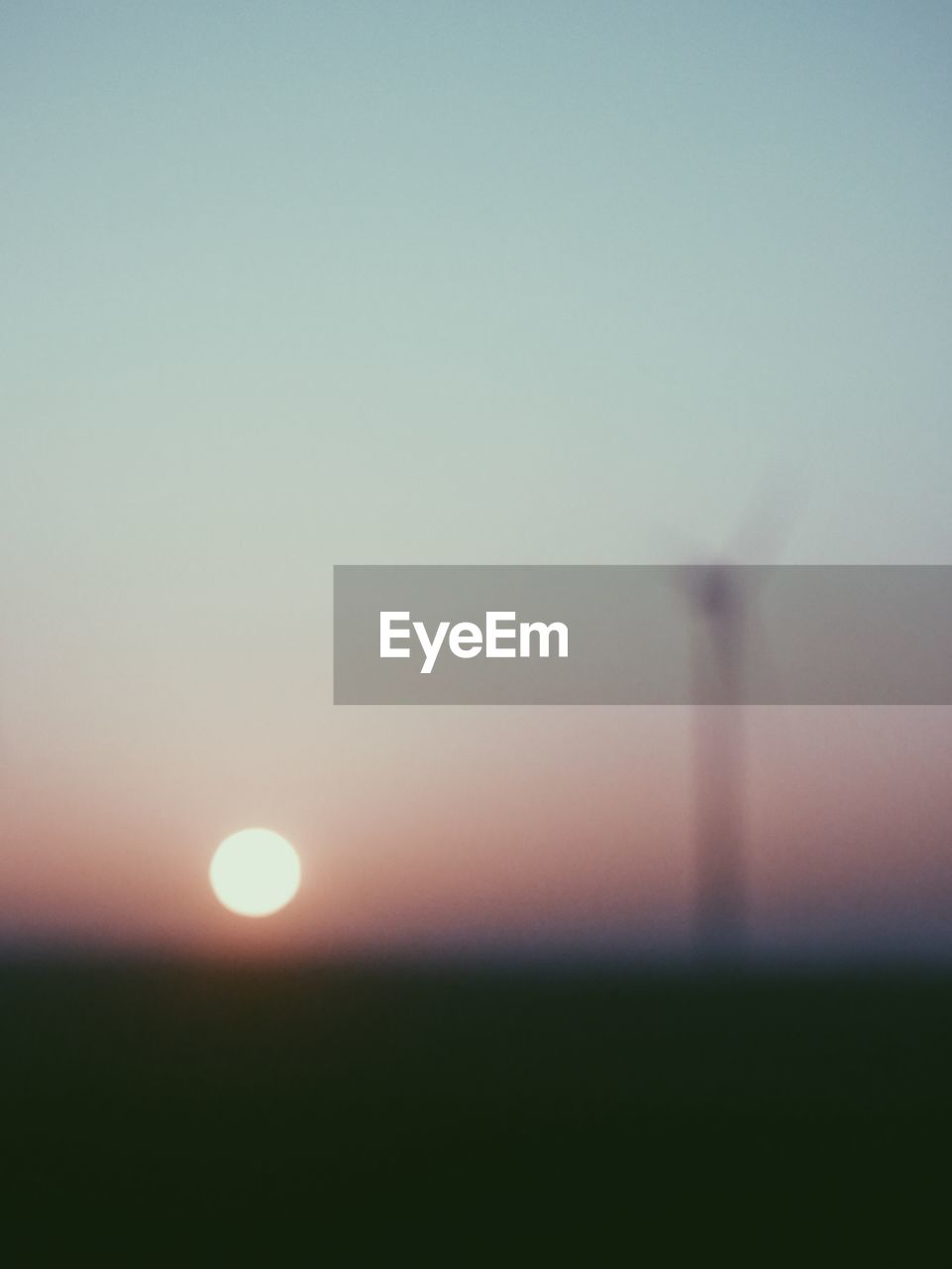 DEFOCUSED IMAGE OF FIELD AGAINST CLEAR SKY DURING SUNSET