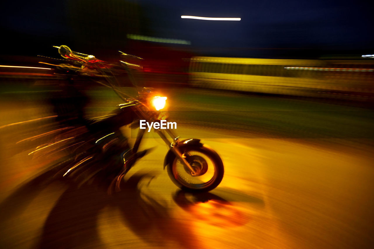 motion, transportation, blurred motion, speed, mode of transportation, night, illuminated, land vehicle, city, long exposure, road, on the move, bicycle, street, one person, architecture, motorcycle, sport, light - natural phenomenon, real people, outdoors, riding