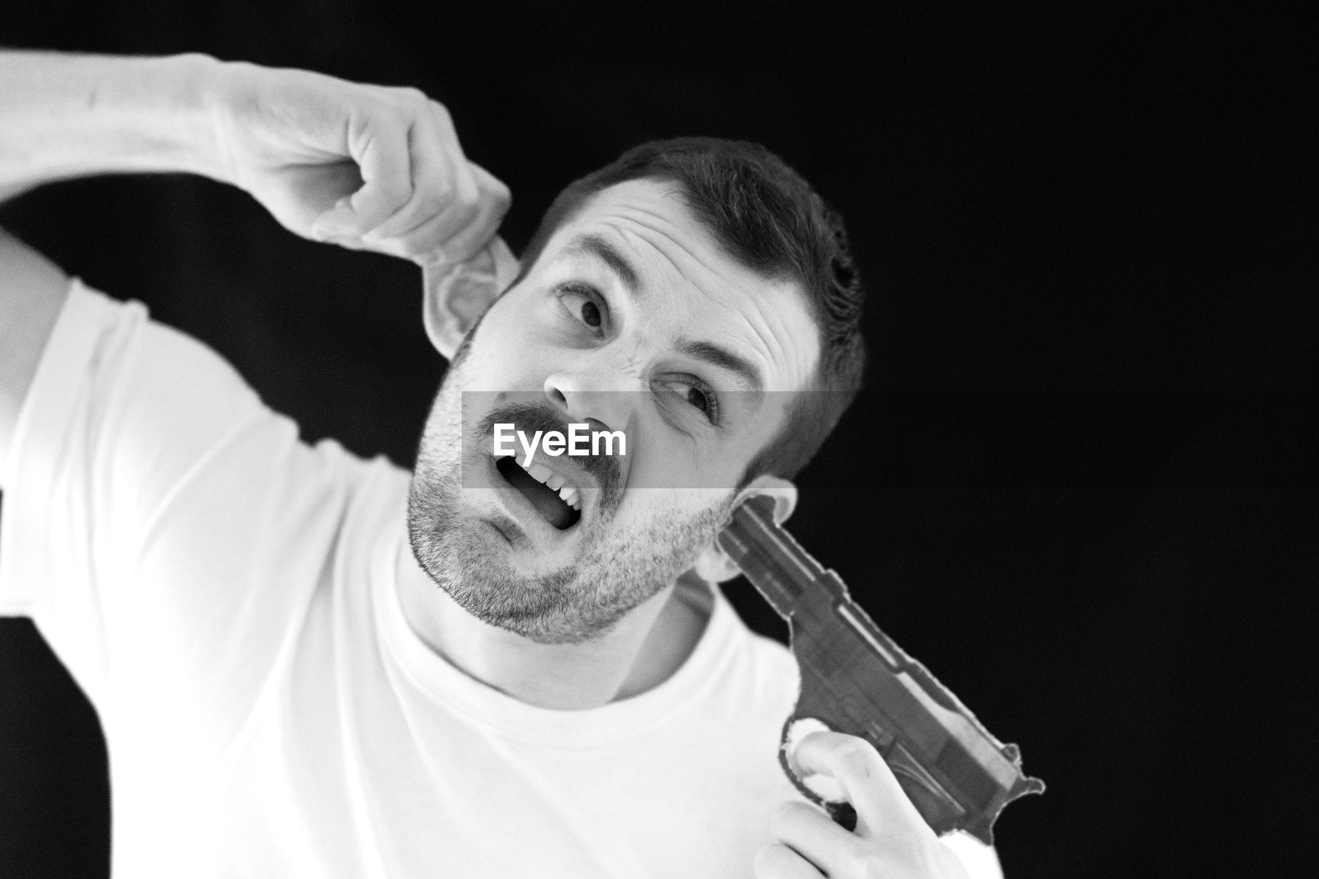 Man pointing gun in ear against black background