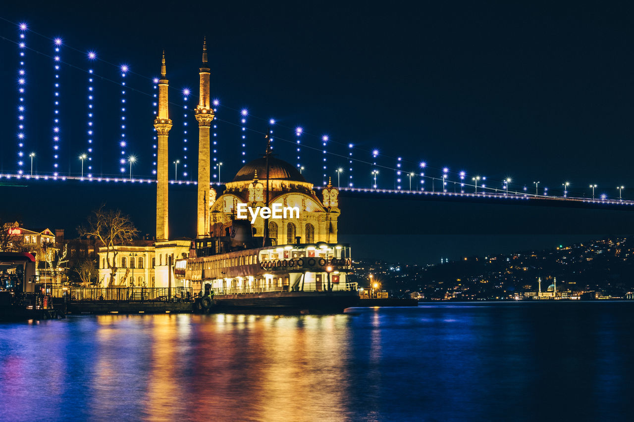 Illuminated ortakoy mosque with bridge in background in istanbul at night