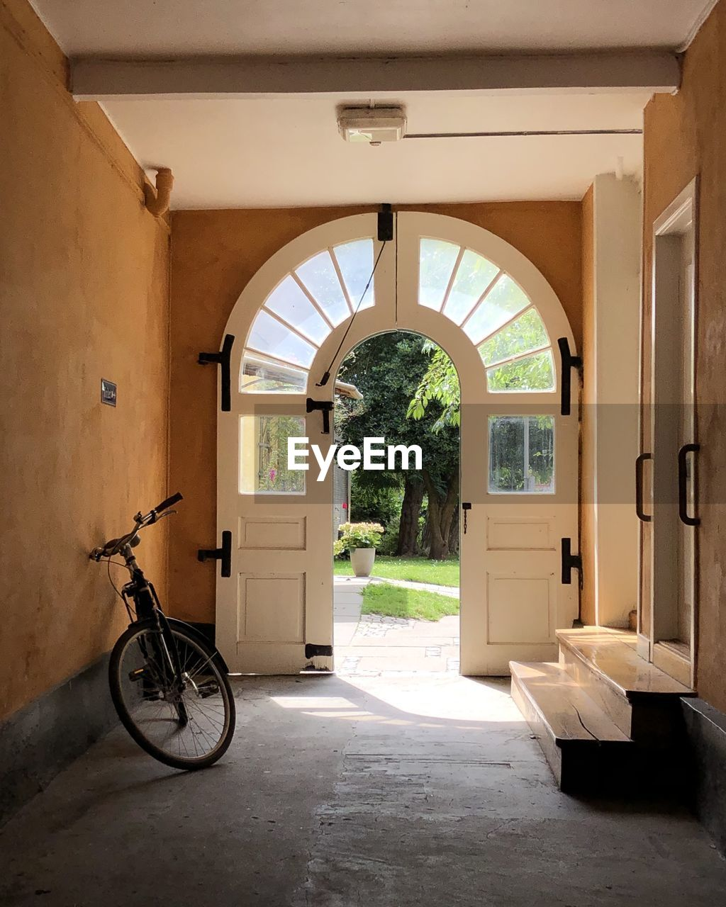 arch, architecture, built structure, bicycle, entrance, building, door, day, building exterior, plant, no people, nature, transportation, land vehicle, sunlight, potted plant, outdoors, wall - building feature, mode of transportation, flooring, architectural column, courtyard