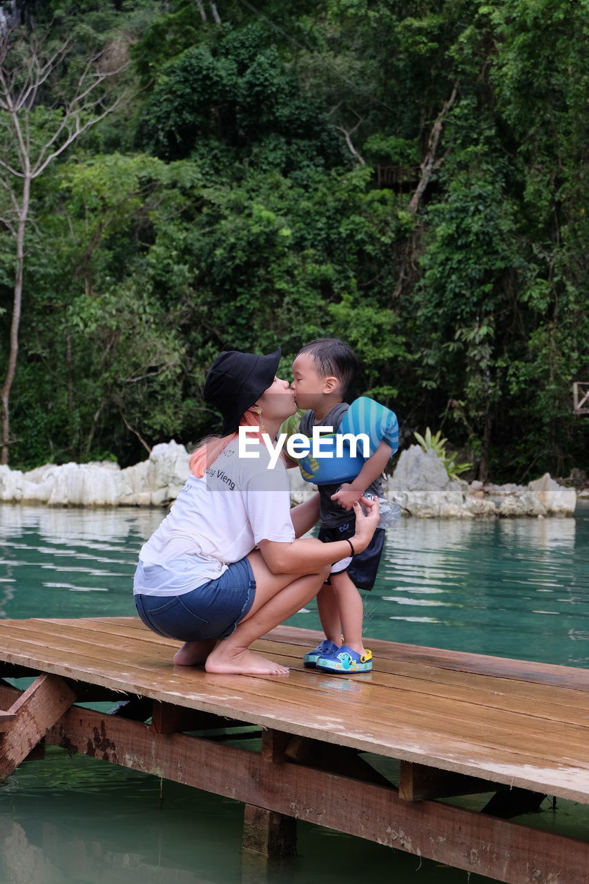 Woman Kissing Son On Pier Over Lake Against Trees