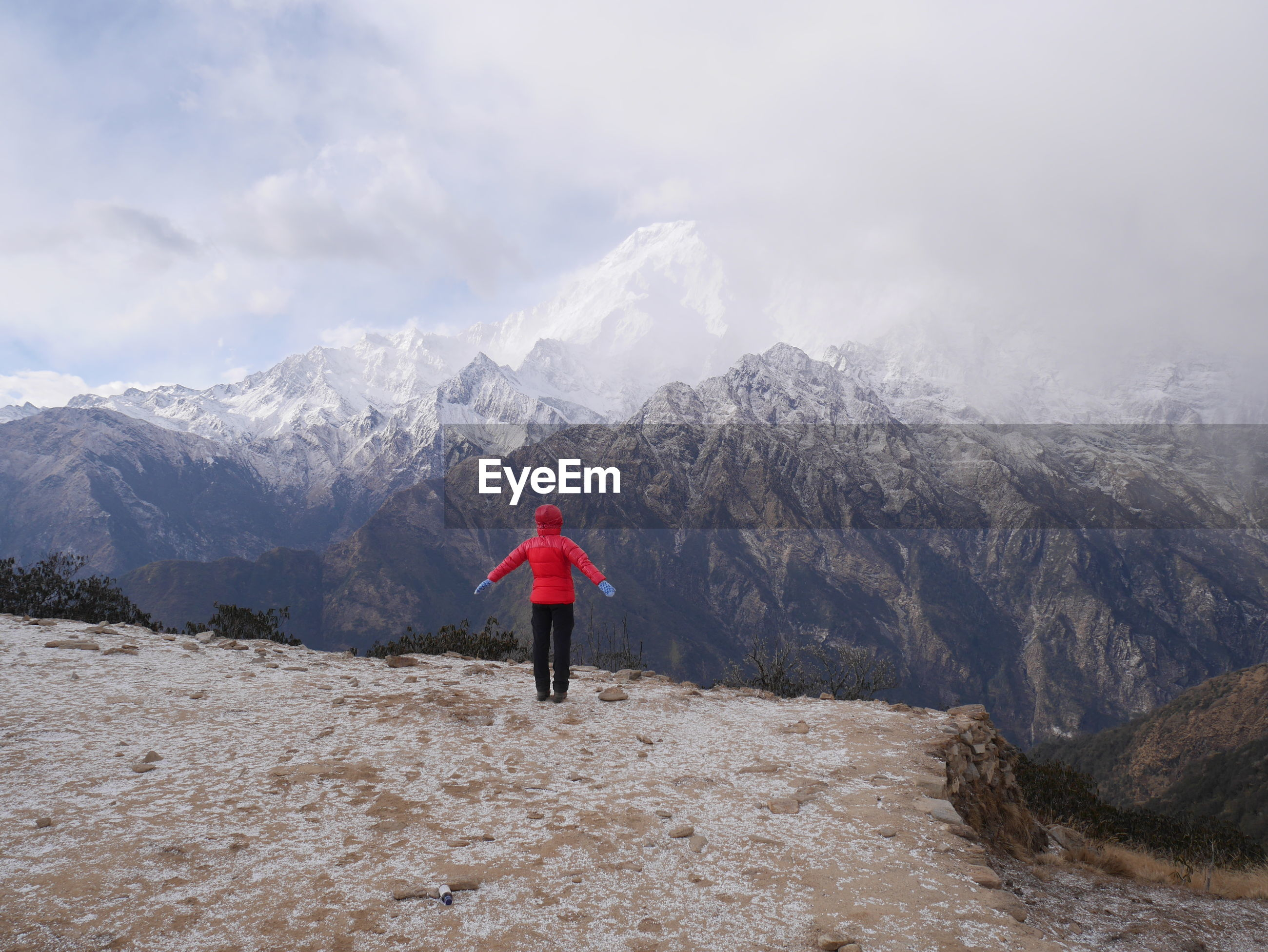 Rear view of person standing on snow covered land against mountains