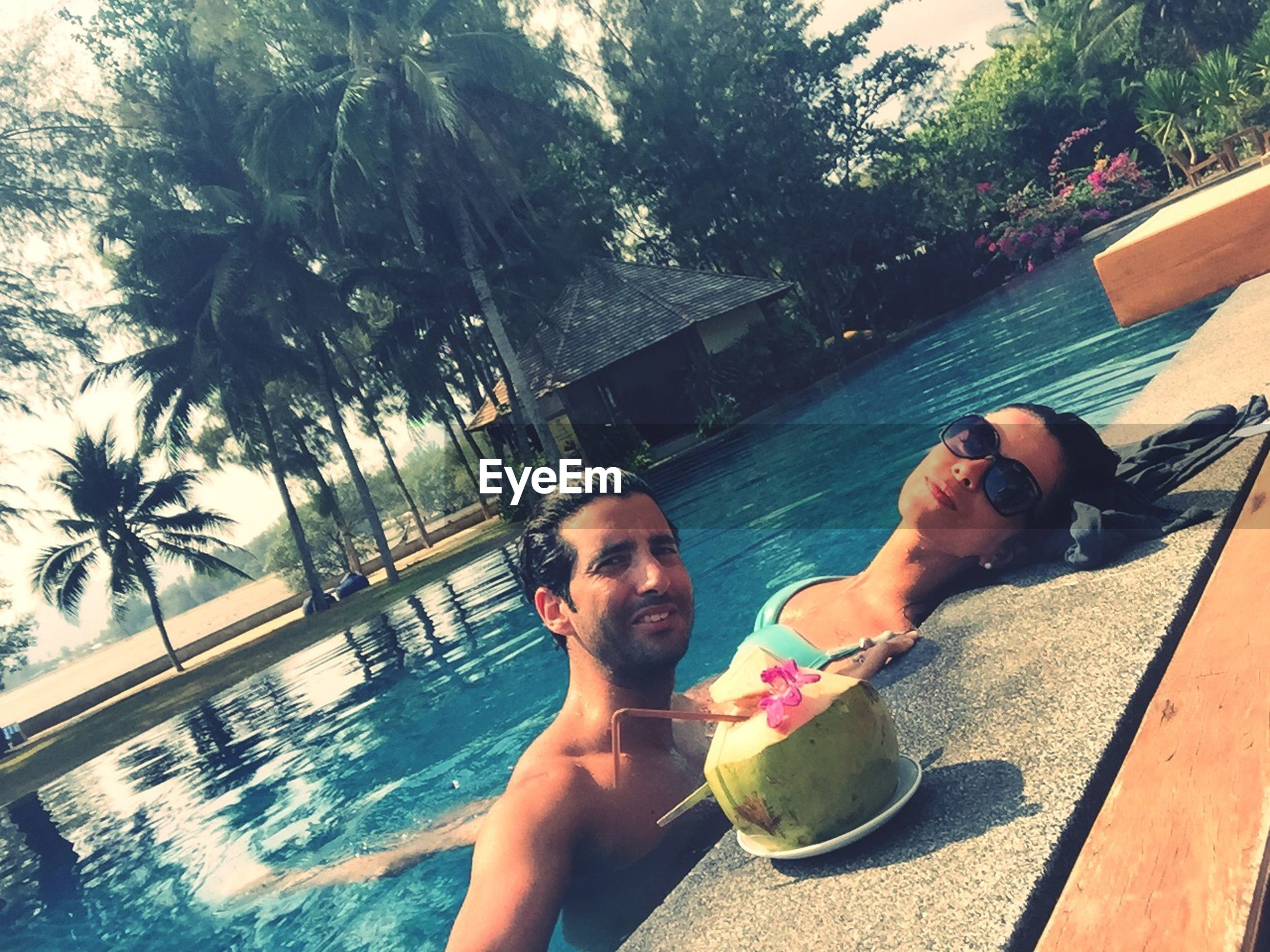 lifestyles, leisure activity, young adult, person, young women, tree, water, swimming pool, casual clothing, sunlight, smiling, full length, sitting, fun, happiness, looking at camera, enjoyment