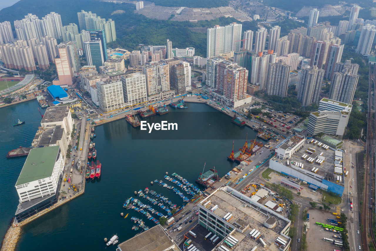 HIGH ANGLE VIEW OF CITY BY SEA AGAINST MODERN BUILDINGS