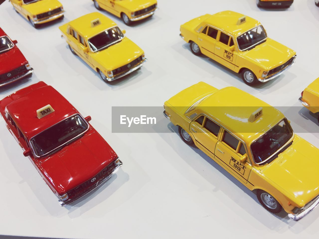 car, motor vehicle, mode of transportation, yellow, toy car, high angle view, transportation, no people, land vehicle, toy, still life, indoors, studio shot, close-up, red, bus, taxi, small, road, school bus