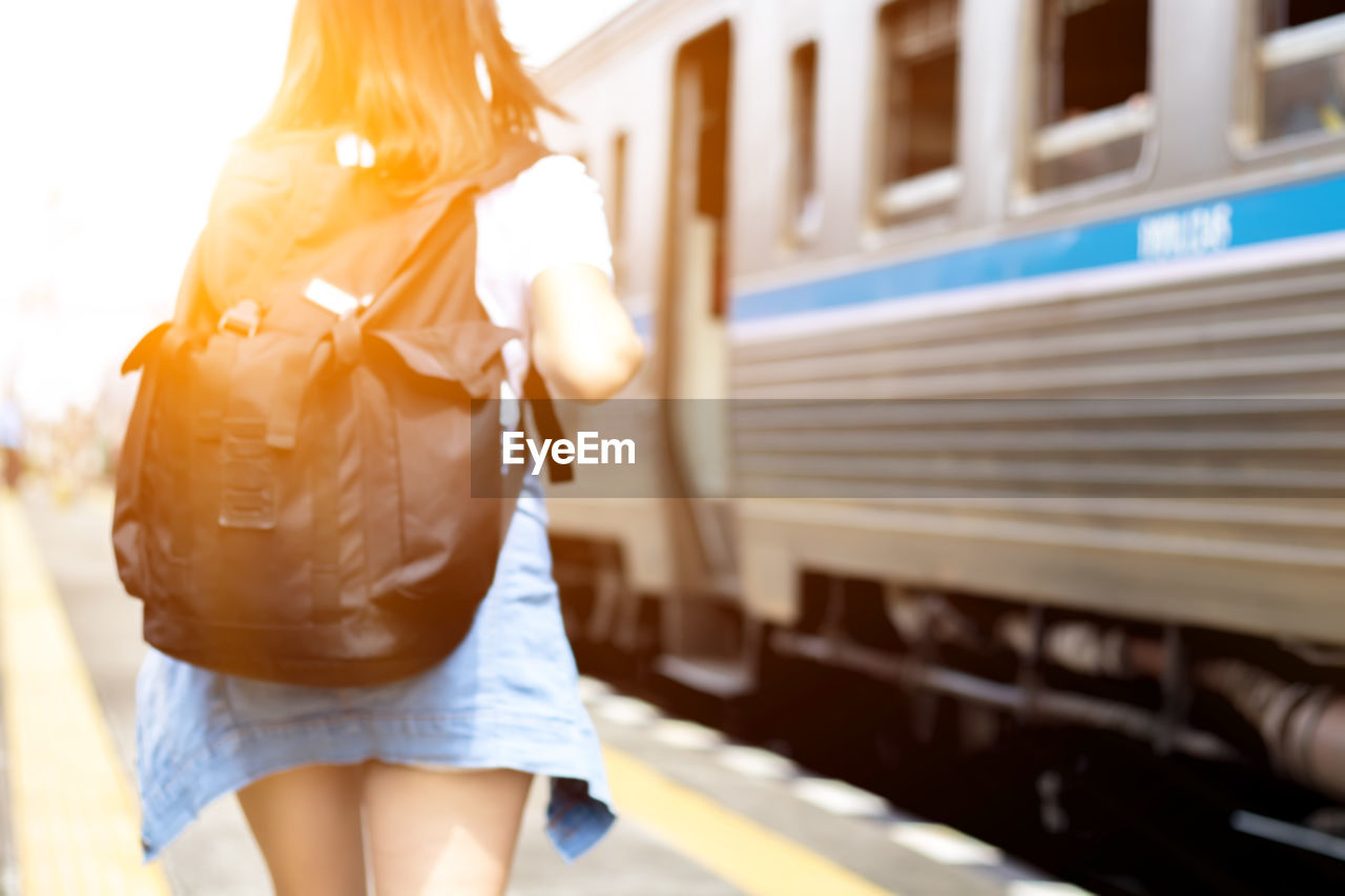 Rear view of woman carrying backpack while standing by train