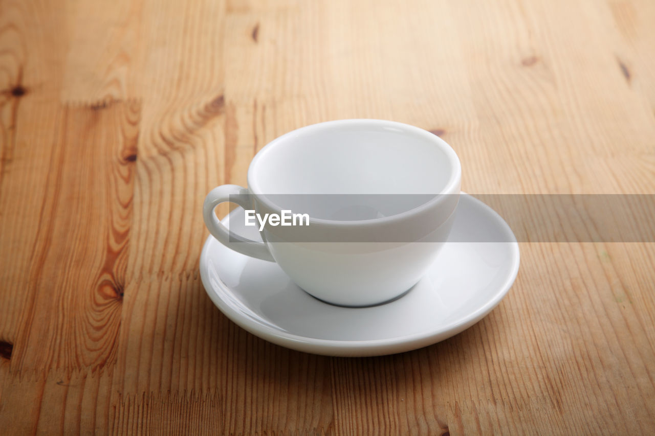 food and drink, cup, drink, refreshment, table, mug, wood - material, white color, still life, saucer, crockery, coffee cup, high angle view, indoors, coffee - drink, no people, coffee, close-up, food, freshness, tea cup, non-alcoholic beverage