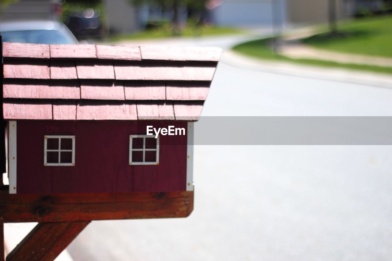 architecture, built structure, focus on foreground, day, house, no people, building exterior, building, nature, outdoors, roof, window, wood - material, road, sunlight, city, close-up, street, selective focus, transportation, roof tile