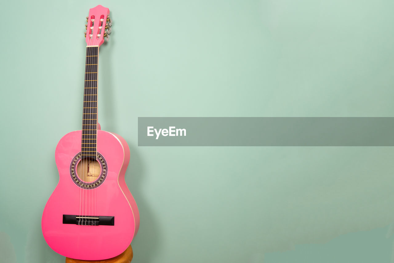 music, musical instrument, string instrument, arts culture and entertainment, guitar, musical equipment, indoors, copy space, colored background, wall - building feature, no people, studio shot, acoustic guitar, string, single object, still life, green background, musical instrument string, cut out, green color, rock music, blue background