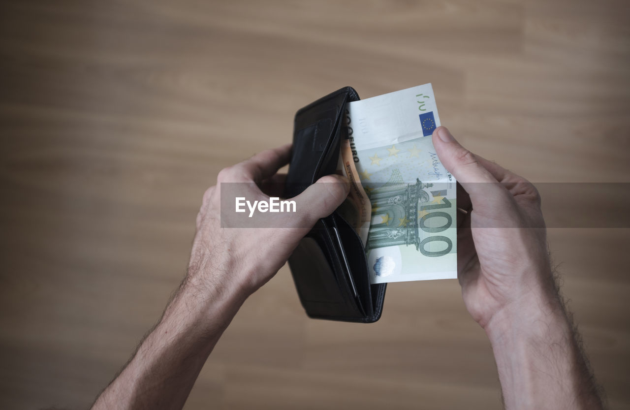 Cropped Hands Removing Paper Currencies From Wallet