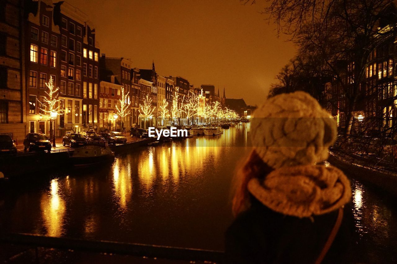 water, architecture, building exterior, nautical vessel, built structure, illuminated, city, reflection, transportation, real people, sky, one person, lifestyles, mode of transportation, nature, river, night, hat, outdoors, warm clothing