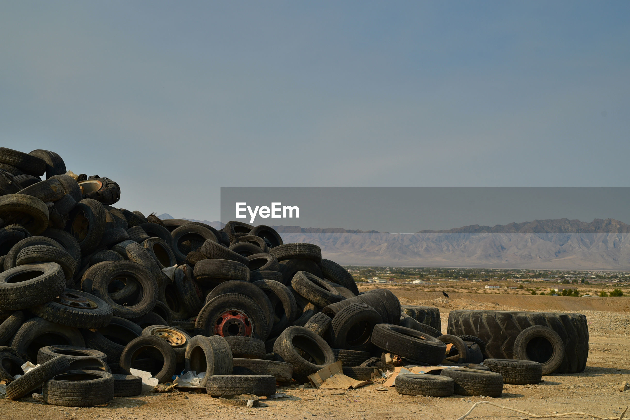Worn-out vehicle tires piled in mojave desert with  distant mountains in pahrump, nevada, usa