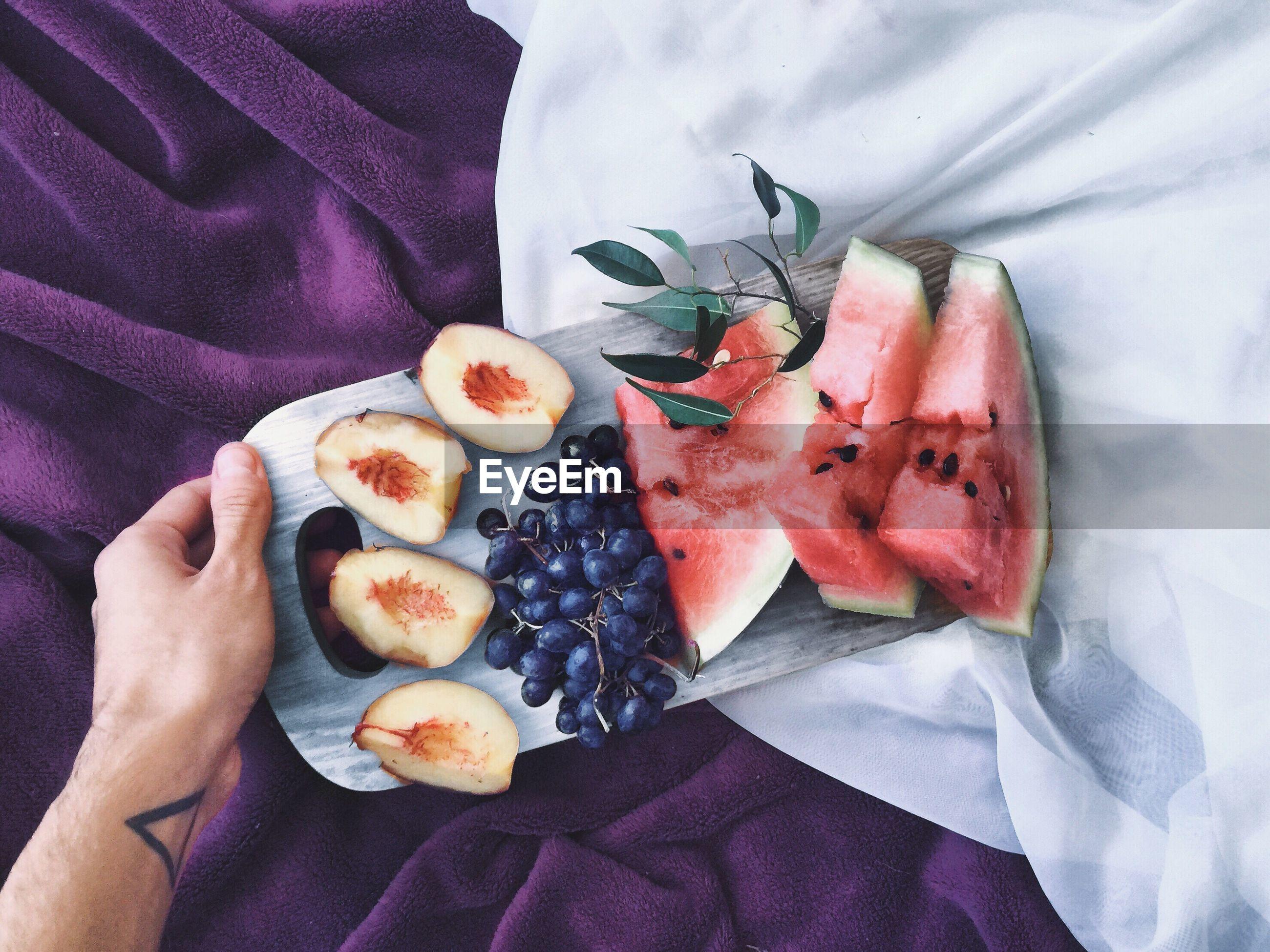 Close-up of hand holding fruit platter