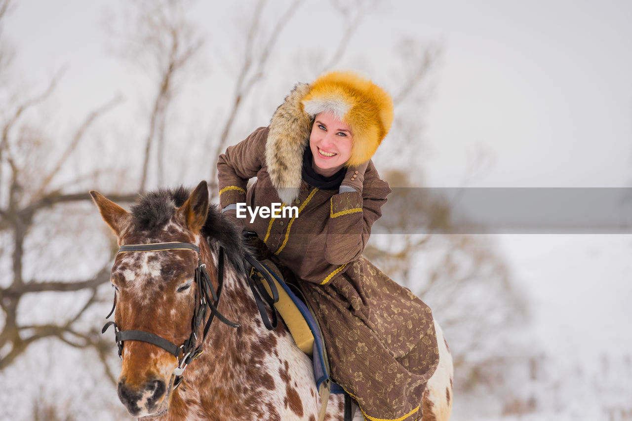 Portrait of smiling woman sitting on horse during winter