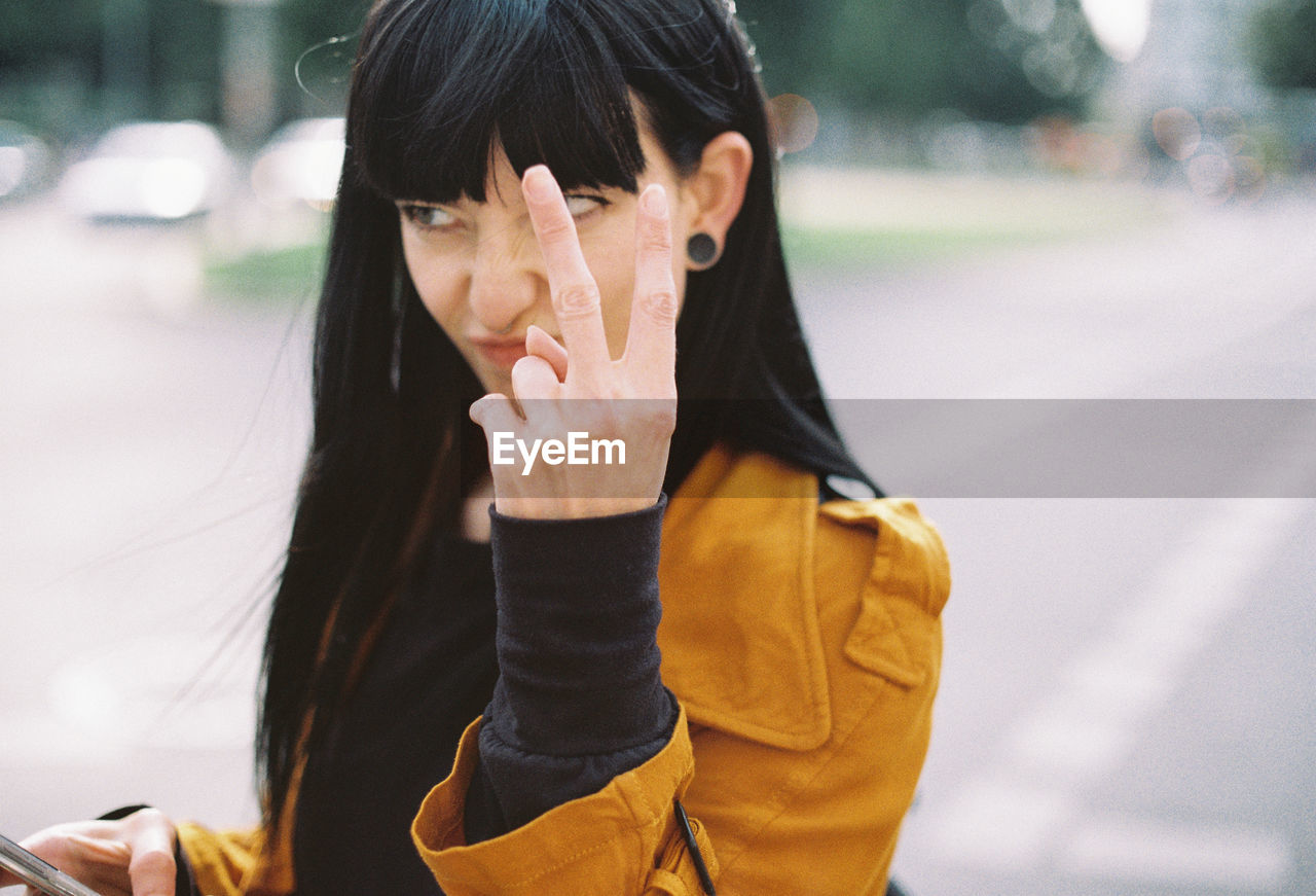 Close-Up Of Young Woman Gesturing Outdoors