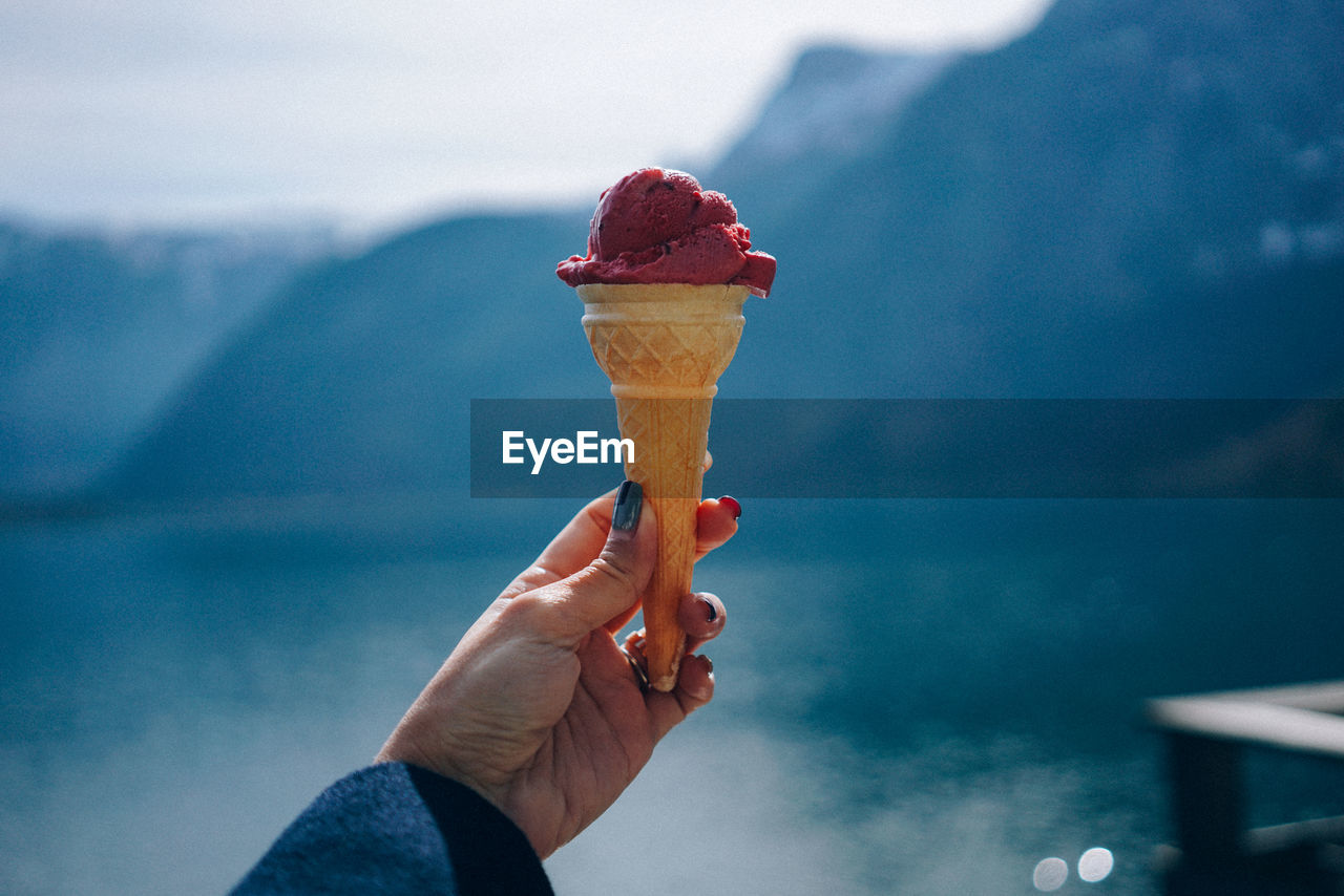 Cropped Hand Of Woman Holding Ice Cream Cone Against Lake