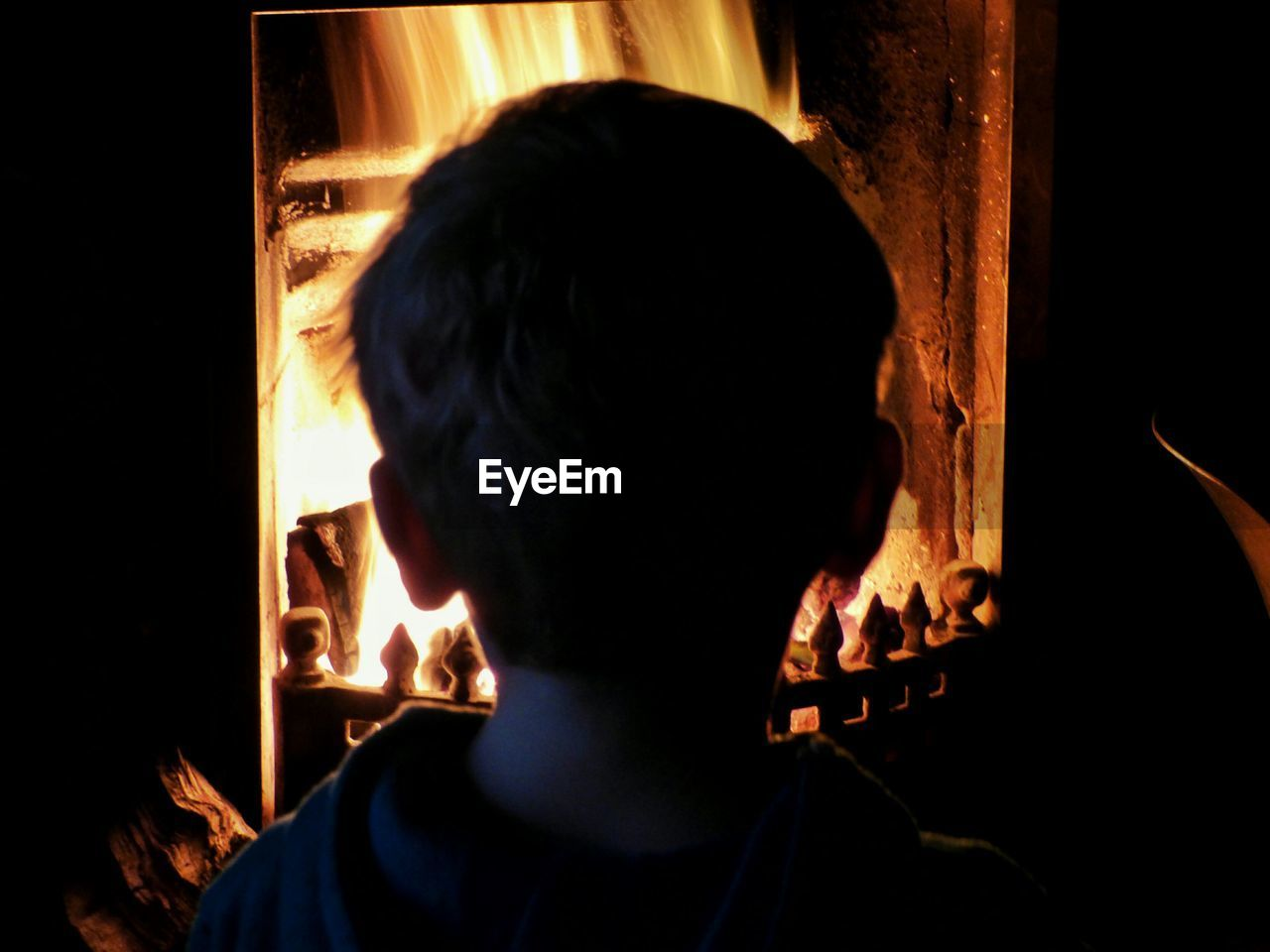 Rear view of boy standing in front of fireplace at home