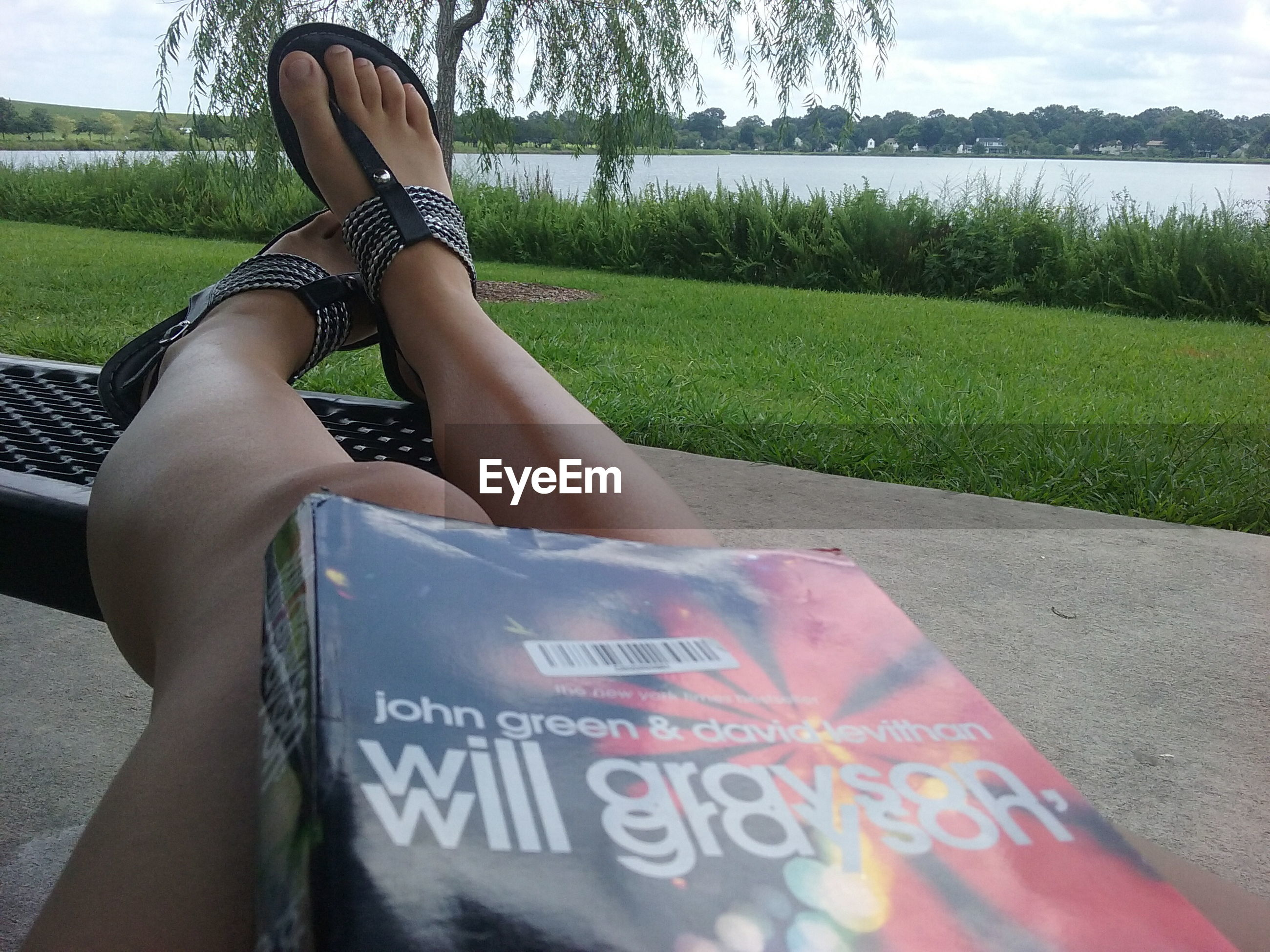 text, western script, grass, lake, relaxation, person, tranquil scene, field, water, tranquility, footpath, outdoors, lying down, growth, day, personal perspective, non-urban scene, young adult, grassy