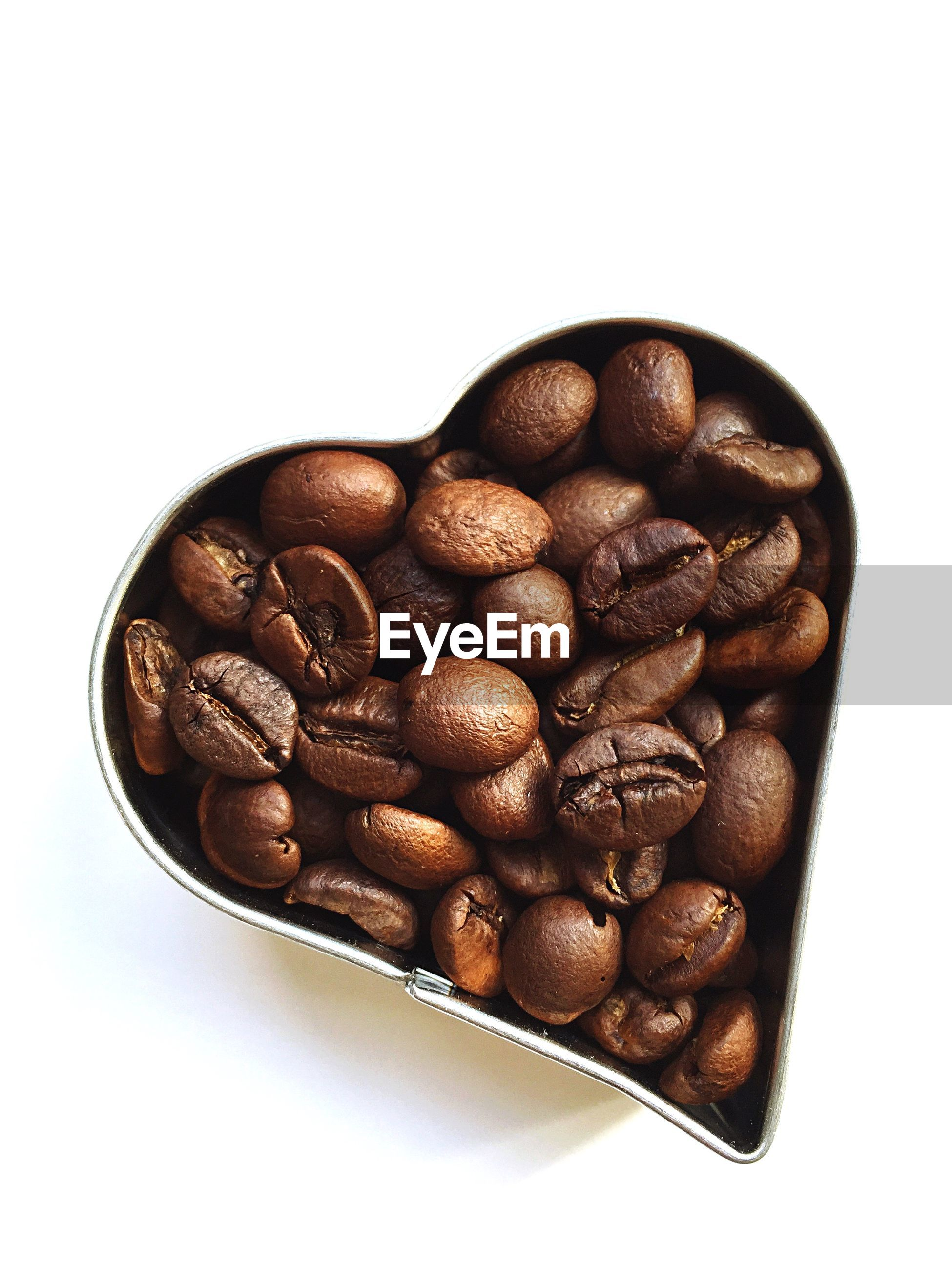 Close-up of coffee beans in heart shape container on white background