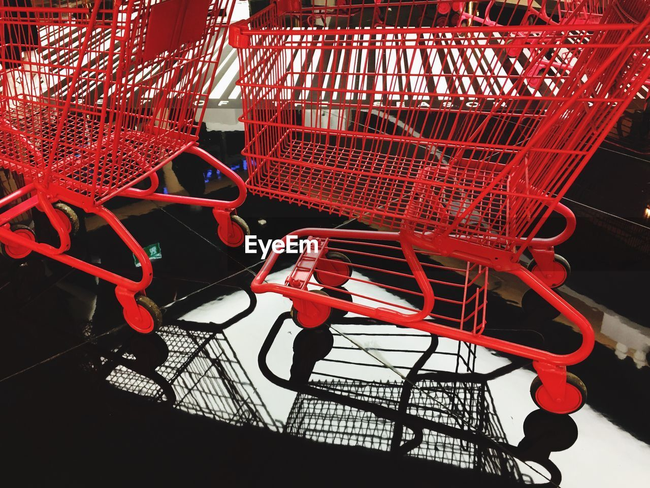 Close-up of red empty shopping carts on tiled floor