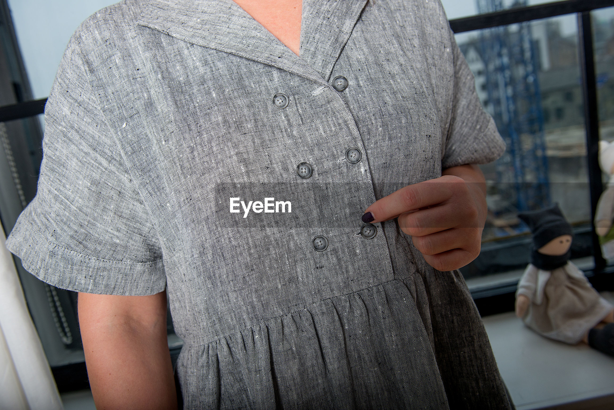 Midsection of woman wearing gray linen dress at home