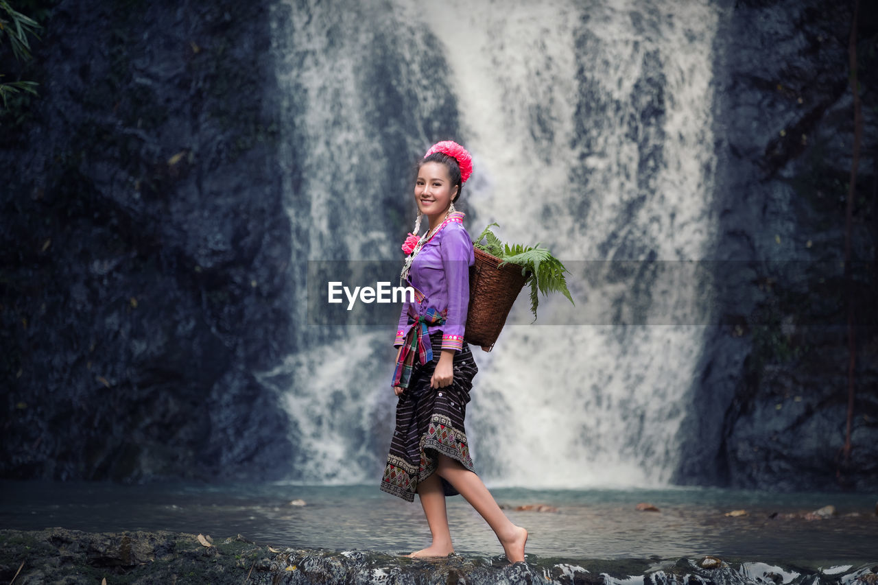 Full Length Portrait Of Young Woman Standing Against Waterfall